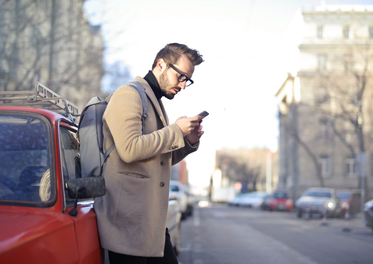 Man on the street looking at mobile phone waiting for ride share car to come to tie in with The CYZL business strategy discussion within the blog